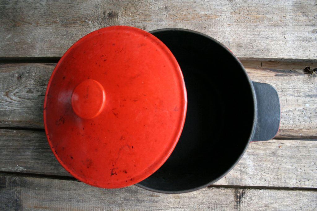 Equipment - Gusseiserner Topf mit halb geöffneten Deckel von oben - Cast iron pot with half-opened lid from above